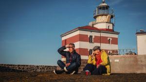 Mies ja nainen risti-istunnassa kalliolla, taustalla punavalkoraidallinen majakka.