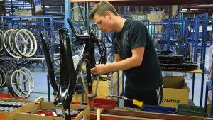 Patrik Lindström trivs på cykelfabriken i Hangö. Lokala avtal har satt punkt för permitteringar och samarbetsförhandlingar tillsvidare.