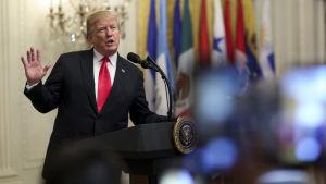 Donald Trump viftar med handen i en talarstol.