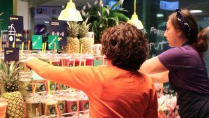 Två kvinnor radar fram smoothies i ett stånd i köpcentret Redi.