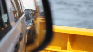 Färjkö syns i sidospegeln på en bil, ombord på en landsvägsfärja.