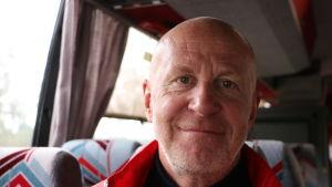 En man i medelåldern sitter i en buss.