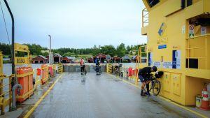 Tre cyklister på en gul landsvägsfärja.
