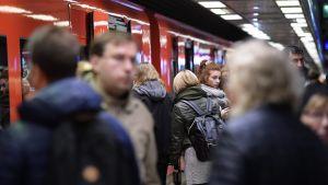 Bild från metrostation under rusningstid. Flera personer rör sig ut och in från metron.