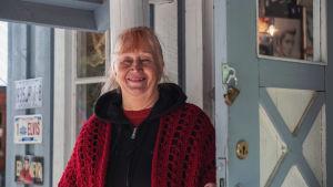 Vaaleansinisen talon ovensuussa punahiuksinen vanhempi nainen, joka on pukeutunut mustaan puseroon, harteilla punainen huivi.