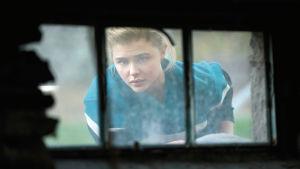 Cameron kikar in genom ett gallerförsett källarfönster.