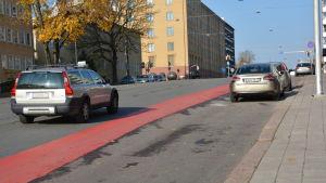 Bilar och ett rött körfält för cyklister.