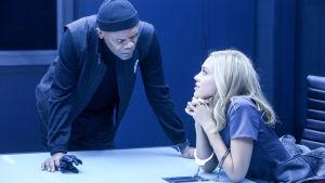 Nainen istuu ja mies nojaa pöytään huoneessa, joka näyttää kuulusteluhuoneelta.