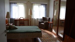 Sovrum med dubbelsäng, fåtölj, skrivbord och två fönster.