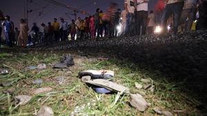 I förgrunden ligger skor strödda över marken, i bakgrunden står människor på järnvägsspår.