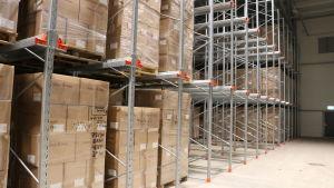 Hundratals lådor uppstaplade på hyllor i ett kyllager.