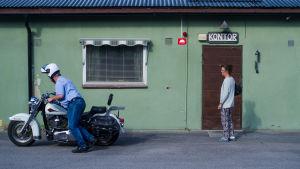Mies lähdössä moottoripyörän selkään. Nainen astumassa vihreäksi maalatun pienen talon ovesta sisään.