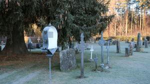 Åsändans begravningsplats i Lappfjärd med äldre och modernare järnkors och gravstenar.