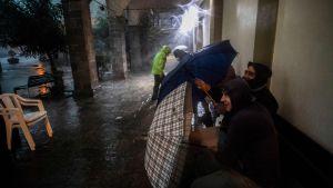Män söker skydd från stormen i Italien.