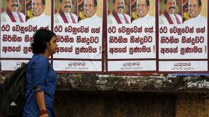 En kvinna går förbi en vägg täckt av planscher på president Sirisena och nya premiärministern Rajapaksa