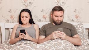 man och kvinna ligger i säng fokuserade på varsin telefon