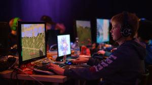 pojke spelar dataspel på lanparty