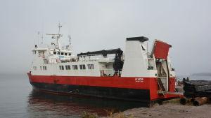 Ett rödvitt fartyg vid stranden med dimma bakom.