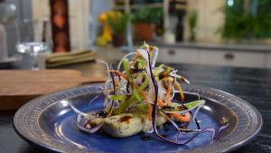 En portion med stekt tofu med enkel teriyakisås och grönsaker i ett kök.