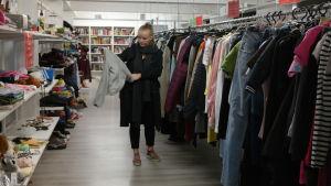 Julia Degerth synar ett plagg på loppmarknad