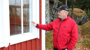 En medelåders man med röd jacka och keps står intill en röd husvägg och pekar på ett fönster.