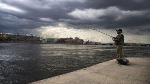 Man som fiskar från stranden av floden Neva i St Petersburg.
