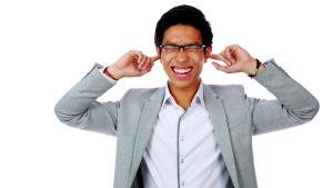 Man som lägger fingrarna i sina öron på grund av hög volym.