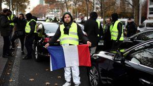 Demonstrant visar upp Frankrikes flagga i samband med protesterna mot höjda bränslepriser.