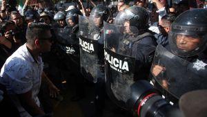 Demonstranter drabbar samman med kravallpolis.