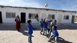 Skolbarn leker med en fotboll på Västbanken.