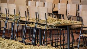 Stolar och bord i matsalen är staplade på varandra. Isoleringsmaterial på golvet och på borden.