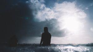 Mies istuu rannalla selkä kameraan