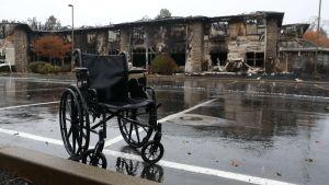 Efterlämnad rullstol i regn framför brandruiner i Paradise, Kalifornien