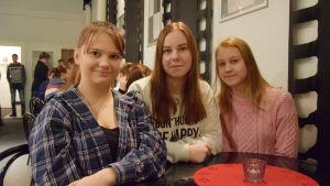 Fanny Konsin, Evelina Forsström och Adeline Uusimäki sitter i en teaterlobby.