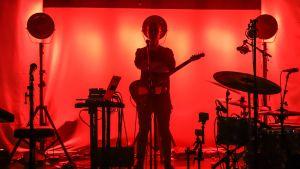 Kitaristi seisoo lavalla eri soittimien keskellä yksin. Punainen tausta.