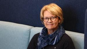 En medelålders kvinna sitta i en blå soffa. Kvinnan har halvlångt ljust hår och glasögon på huvudet. Runt halsen har hon en blå halsduk.