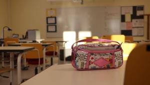 En penal ligger på ett bord i ett klassrum.