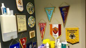 Vimplar av olika fotbollslag hänger på väggen.