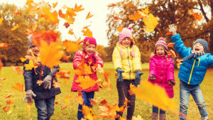 Barn leker med höstlöv