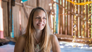 Natural High Healing Festivalin johtaja Henna Länsipää hymyilee ja katsoo ohi kamerasta