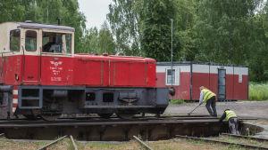 Kaksi keltaisiin liiveihin pukeutunutta miestä työntävät junan kääntöpöytää, jolla seisoo iso punainen veturi.