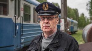 Vanhempi mies, jolla on päässään konduktöörinlakki. Taustalla sinisiä junavaunuja.