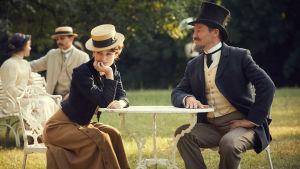 Willy och Colette samtalar vid ett litet bord i parken.