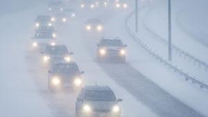 Bilar i snöyra på landsväg