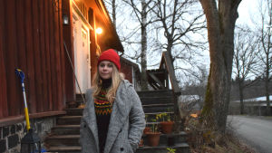 kvinna framför äldre trähus