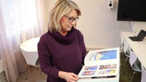 Johanna Grönberg bläddrar i bok.