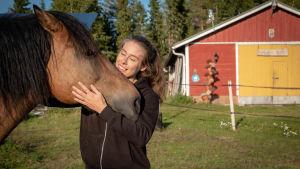 En kvinna står och kelar med en häst.