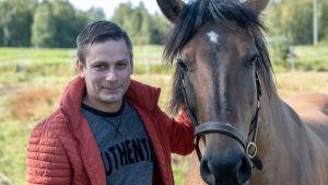 En man står bredvid en häst och småler.