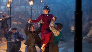 MAry Poppins lyfts upp av två sotare.