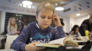 Lapsi lukee kuoluluokassa